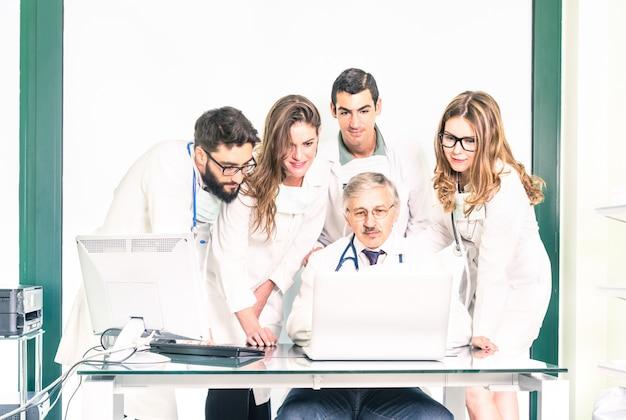 Grupo de jovens estudantes de medicina com médico sênior na clínica de cuidados de saúde