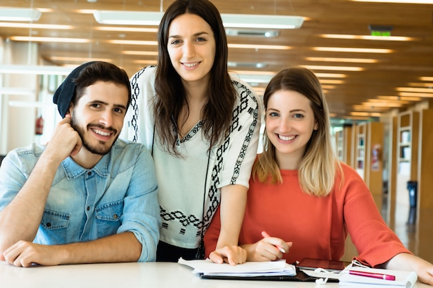 Grupo de jovens estudantes estudando juntos na biblioteca.