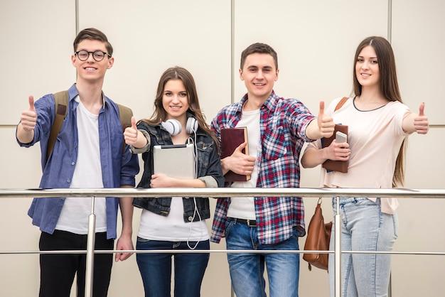 Grupo de jovens estudantes felizes aparecendo os polegares.