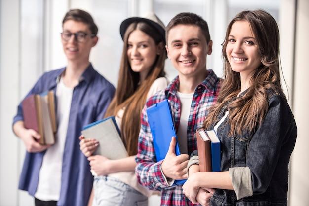 Grupo de jovens estudantes felizes em uma faculdade.