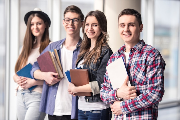 Grupo de jovens estudantes felizes em uma universidade.
