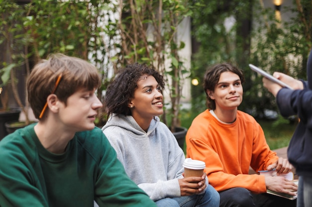 Grupo de jovens estudantes sentados com café para viagem e livros nas mãos enquanto estudam juntos no pátio da universidade