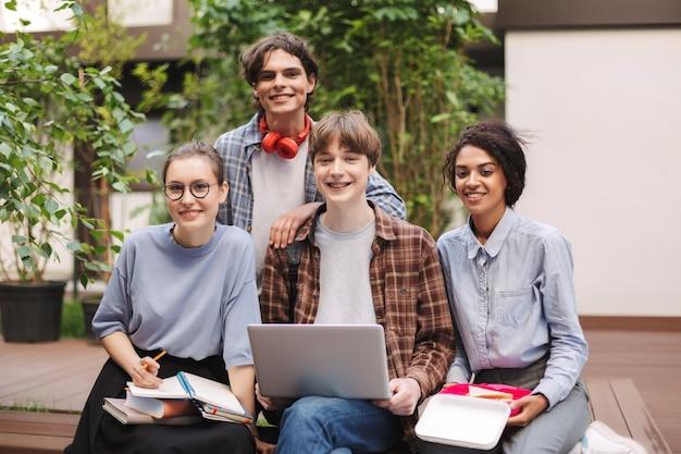 Grupo de jovens estudantes sorridentes, sentados no banco com livros e laptop sobre os joelhos e estudando juntos enquanto felizes
