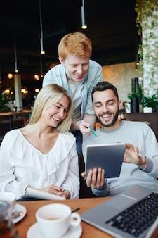Grupo de jovens estudantes universitários rindo de coisas engraçadas na tela do touchpad enquanto navegam pelas informações em uma reunião em um café