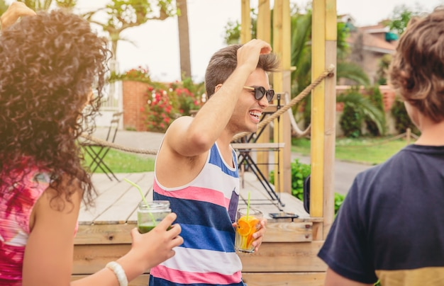 Grupo de jovens felizes com bebidas saudáveis, se divertindo em uma festa de verão ao ar livre. conceito de estilo de vida dos jovens.
