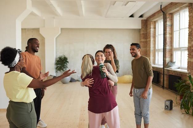 Grupo de jovens felizes cumprimentando-se, abraçando-se e conversando em pé no estúdio de dança