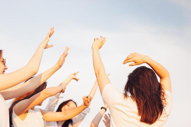Grupo de jovens felizes dançando meninas bronzeadas no fundo do céu azul, horário de verão