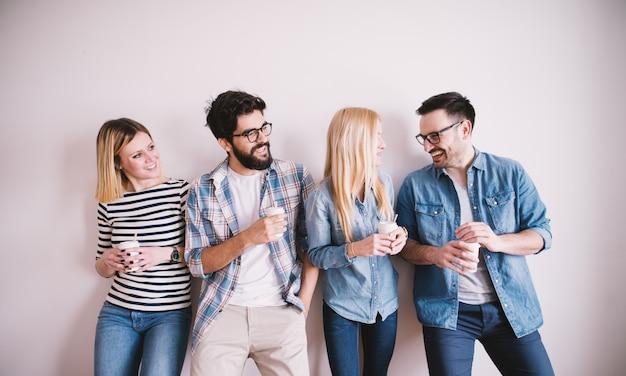 Grupo de jovens felizes elegantes inclinando-se contra a parede em uma pausa e juntos bebe café no copo de papel.