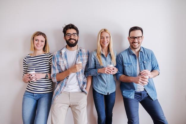 Grupo de jovens felizes em pé contra a parede e segurando o café para ir. arranque o conceito do negócio.