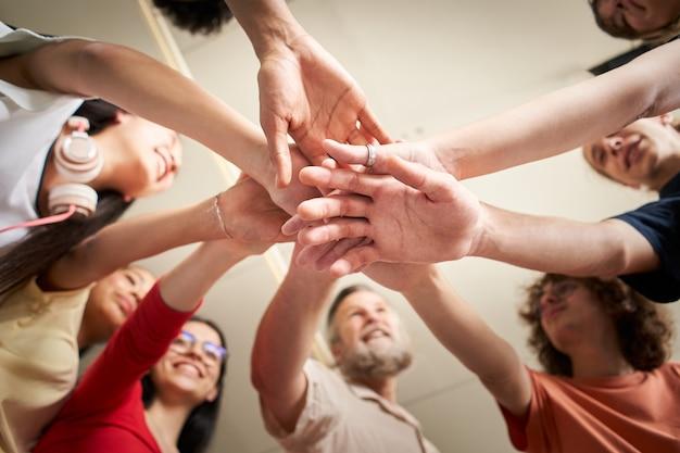 Grupo de jovens felizes fazendo uma torre com as mãos na vista de baixo