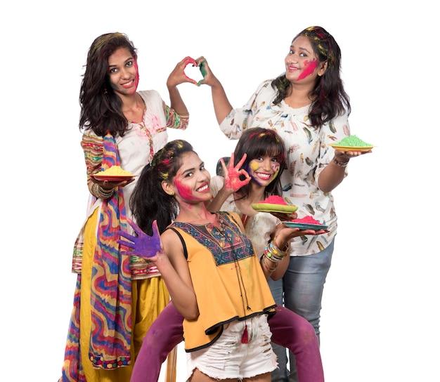 Grupo de jovens felizes se divertindo com o pó colorido no festival de cores holi