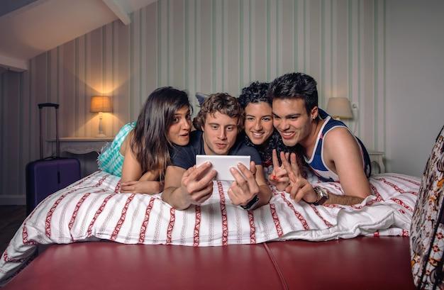Grupo de jovens felizes tirando foto com um smartphone deitado sobre a cama. conceito de estilo de vida dos jovens.