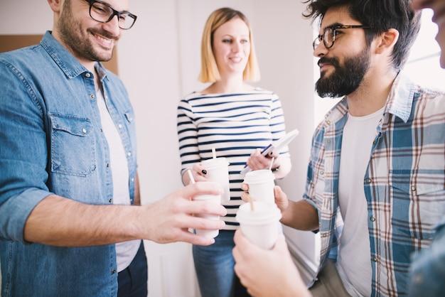 Grupo de jovens funcionários felizes casuais na pausa juntos bebe café no copo de papel.