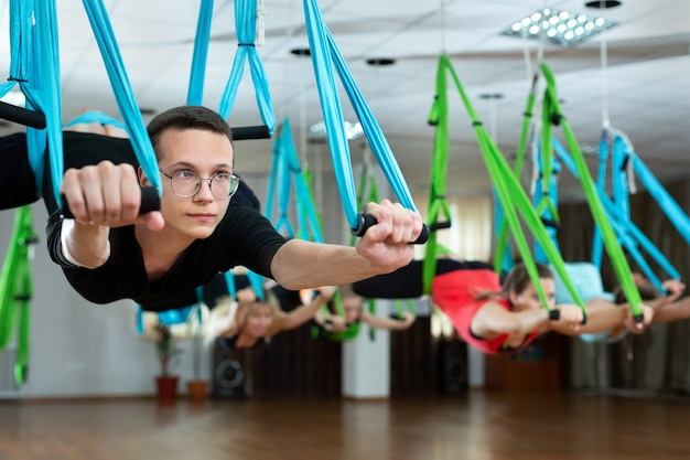 Grupo de jovens homens e mulheres fazem ioga aérea em redes em um clube de fitness.