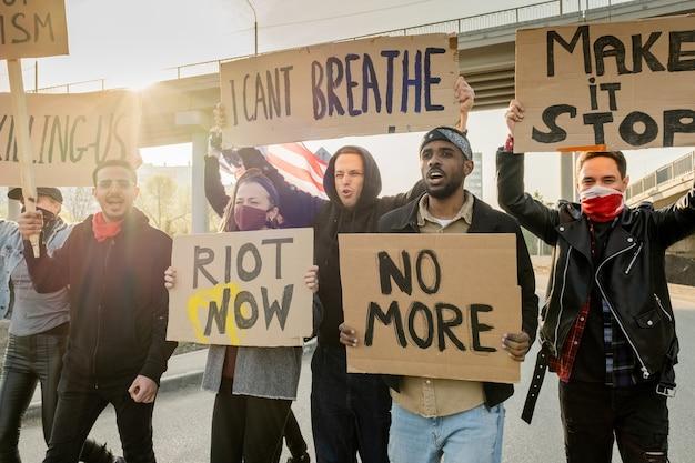 Grupo de jovens inter-raciais irritados carregando cartazes e caminhando pela rua enquanto reivindicam direitos iguais
