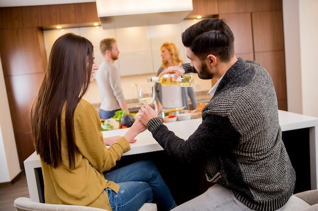Grupo de jovens jantando e bebendo vinho na cozinha moderna