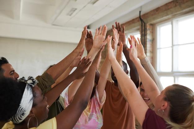 Grupo de jovens levantando as mãos e apoiando uns aos outros durante o treinamento