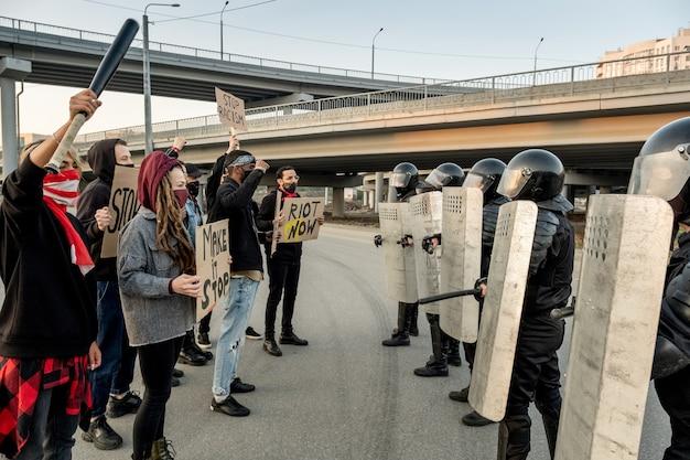 Grupo de jovens manifestantes com máscaras segurando cartazes e em frente aos guardas da polícia com escudos