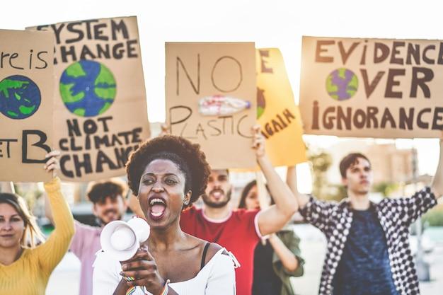 Grupo de jovens manifestantes na estrada, jovens de diferentes culturas e raças lutam pela poluição plástica e pelas mudanças climáticas - conceito do aquecimento global e do meio ambiente - foco no rosto da garota africana