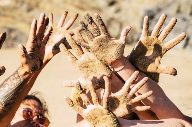 Grupo de jovens mostrando e brincando com as mãos sujas na praia durante