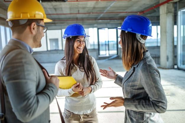 Grupo de jovens motiva altamente atraentes arquitetos caucasianos com capacetes nas cabeças em pé no edifício em processo de construção e tendo uma conversa casual em pausa.