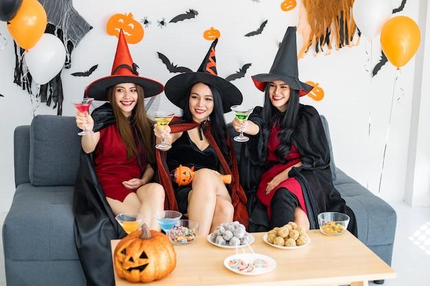 Grupo de jovens mulheres asiáticas fantasiadas que celebram a festa na sala para o tema halloween em casa. gangue adolescente tailandesa para comemorar a festa de halloween com um sorriso. conceito de festa de halloween em casa.