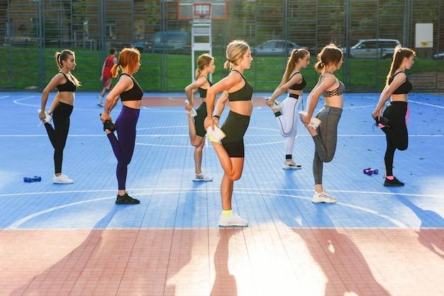 Grupo de jovens mulheres desportivos estão praticando a lição de ioga em pé no exercício vrksasana. as meninas estão equilibrando no tapete de ioga em uma perna ao amanhecer em pose de árvore com gesto namaste