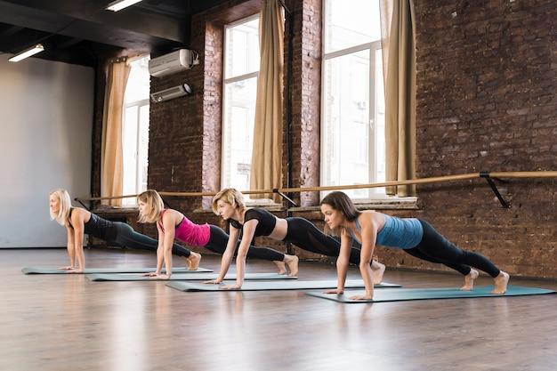 Grupo de jovens mulheres exercitando juntos