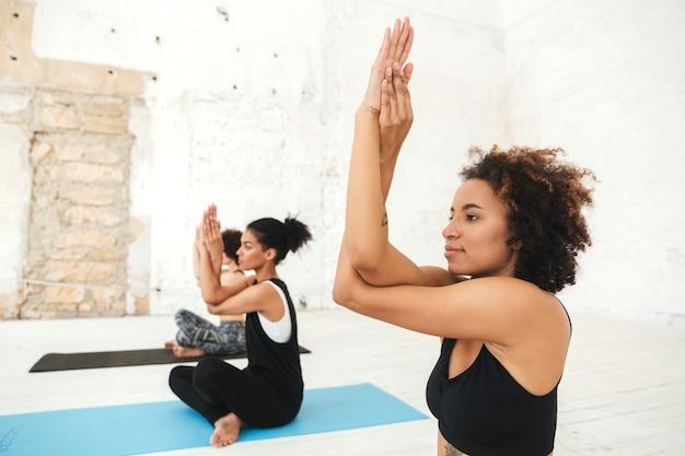 Grupo de jovens mulheres fazendo yoga, exercícios de alongamento