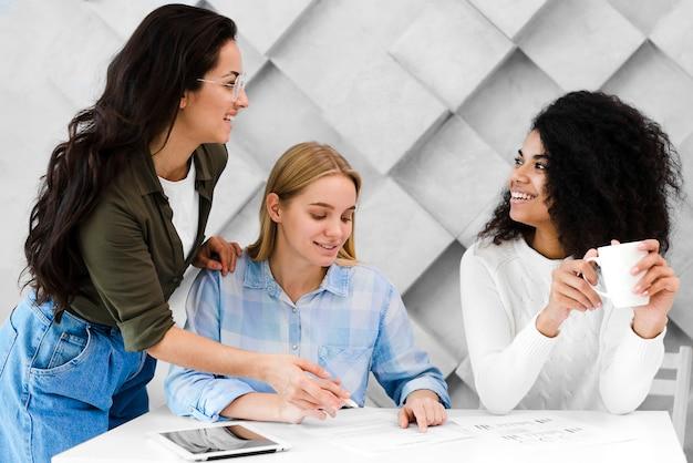 Grupo de jovens mulheres positivas trabalhando juntos