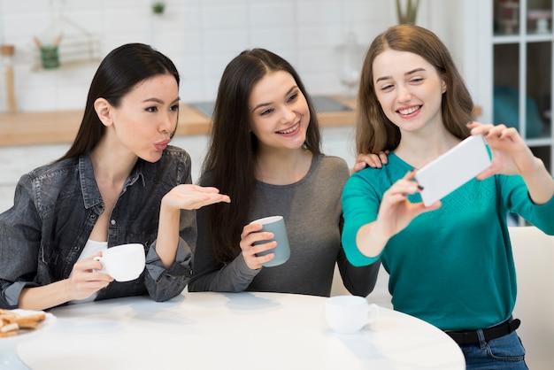Grupo de jovens mulheres tomando uma selfie juntos