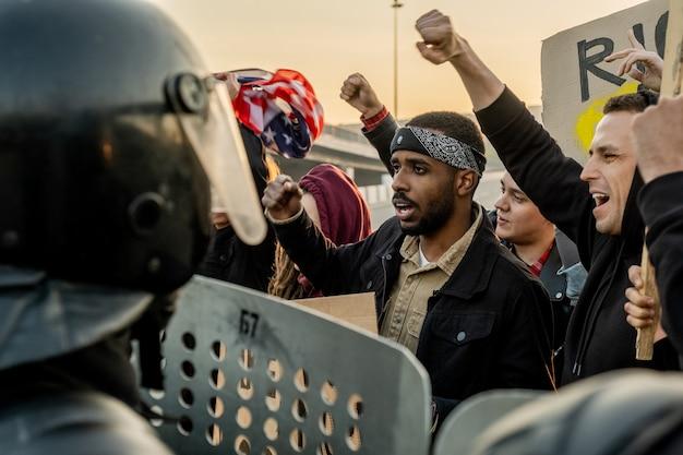 Grupo de jovens multi-étnicos descontentes levantando os braços e gritando, protegendo o discurso durante uma rebelião, enquanto enfrentam a polícia com escudos