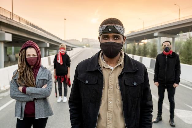 Grupo de jovens multiétnicos descontentes em trajes casuais, movendo-se pela rua enquanto reivindicam seus direitos