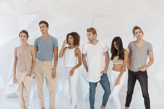 Grupo de jovens multiétnicos lindos vestindo roupas casuais, sorrindo e se divertindo