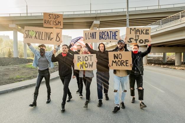 Grupo de jovens multiétnicos raivosos levantando faixas de papelão enquanto protestavam contra o racismo em manifestações de rua