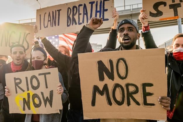 Grupo de jovens multiétnicos rebeldes com faixas levantando os punhos e gritando na rua durante o comício