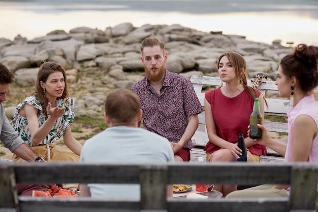 Grupo de jovens passando a noite de verão ao ar livre, sentados à mesa com comida e bebidas, conversando e curtindo o tempo juntos