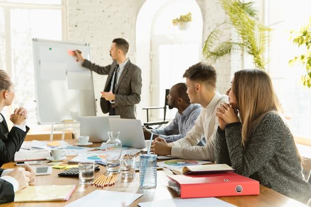 Grupo de jovens profissionais de negócios em um escritório criativo de reunião