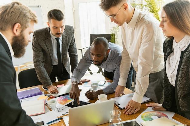 Grupo de jovens profissionais de negócios em uma reunião. diversos grupos de colegas de trabalho discutem novas decisões, planos futuros e estratégias. reunião criativa e local de trabalho, negócios, finanças, trabalho em equipe.