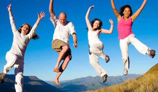 Grupo de jovens pulando no campo conceito