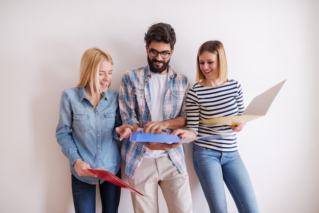 Grupo de jovens que estão e que olham os dobradores que realizam nas mãos ao estar contra a parede branca. arranque o conceito do negócio.