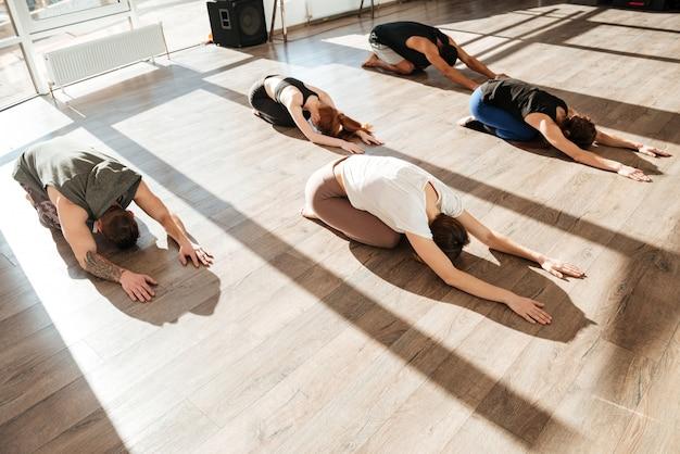 Grupo de jovens relaxados fazendo yoga asana em estúdio