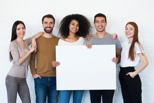 Grupo de jovens segurando um cartaz