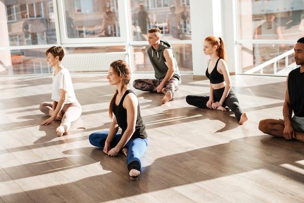 Grupo de jovens sentados e fazendo yoga, exercícios de alongamento