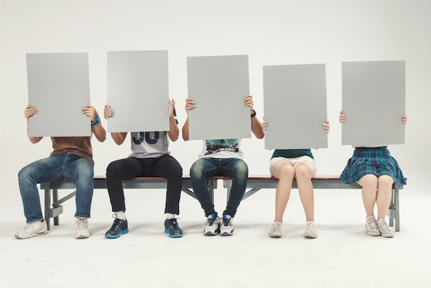 Grupo de jovens sente-se segurando, tiro de estúdio de placa de sinal em branco