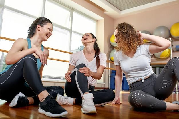 Grupo de jovens sorridentes desportivos, sentado no chão
