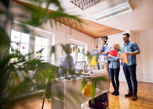 Grupo de jovens sorridentes e confiantes em pé em uma fila com uma pasta na mão antes de uma entrevista com o empresário na frente