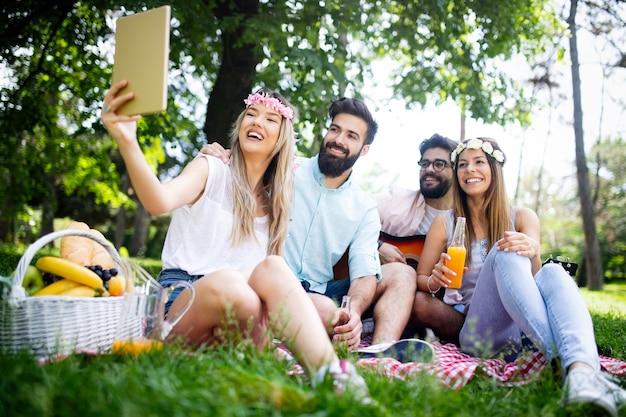 Grupo de jovens tirando selfie ao ar livre, fazendo piquenique, se divertindo