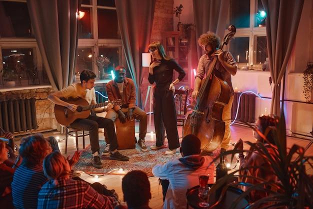 Grupo de jovens tocando instrumentos musicais e cantando durante a apresentação para as pessoas no estúdio