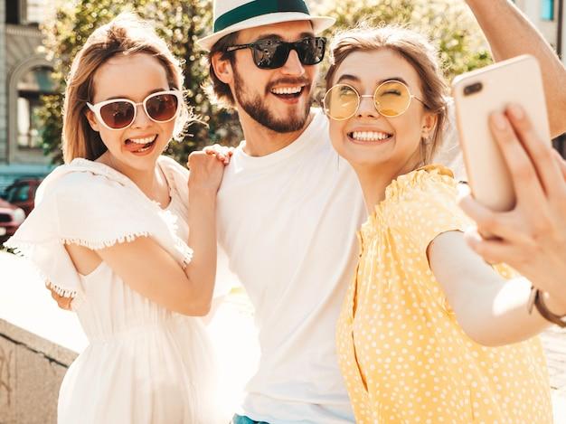 Grupo de jovens três amigos elegantes na rua. homem e duas miúdas giras vestidas com roupas de verão casual. modelos sorridentes se divertindo em óculos de sol. mulheres e cara fazendo foto selfie em smartphone